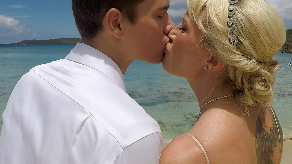 Cincinnati wedding photographer captures image of man and woman kissing in the beach.