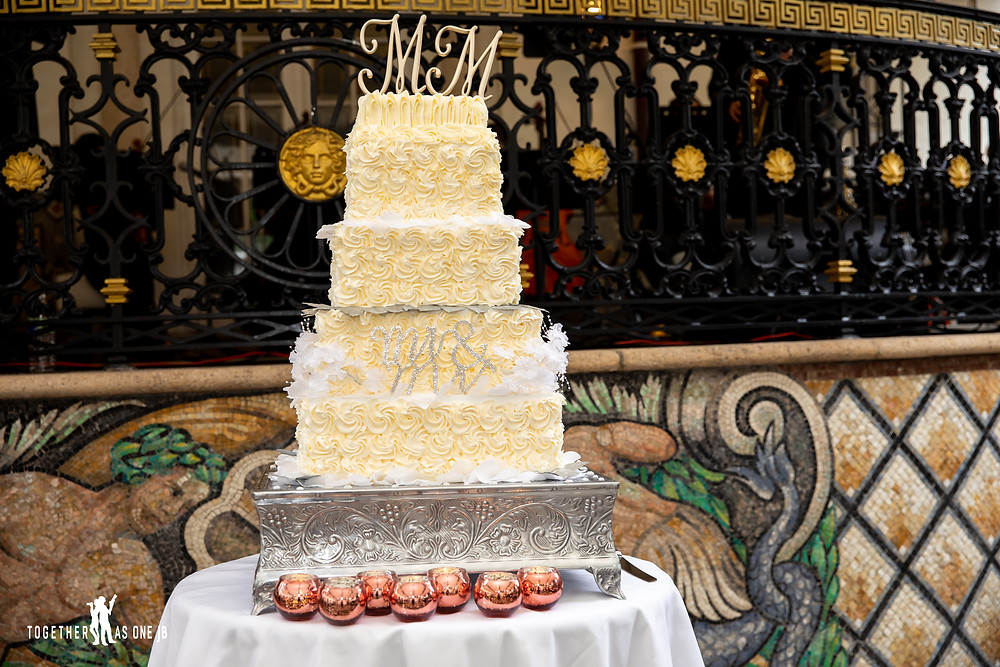 photograph of wedding cake in front of Versace symbol