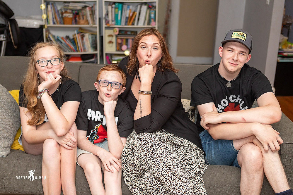 Cincinnati family photographer captures quirky image of family posing in sofa smiling in living room.
