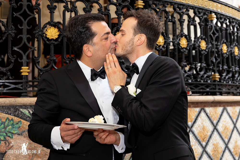 Grooms sharing a kiss after eating first bites of wedding cake