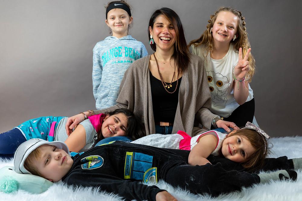 Cincinnati portrait photographer captures image of woman  sitting around a group of kids smiling.