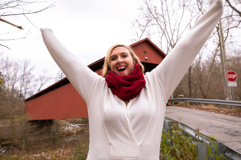 Cincinnati portrait photographer captures image of woman with long sleeved jacket happily smiling in winter.