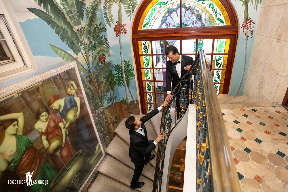 Groom reaches for his husband in famous steps of Versace Mansion with murals on walls and big stained glass window