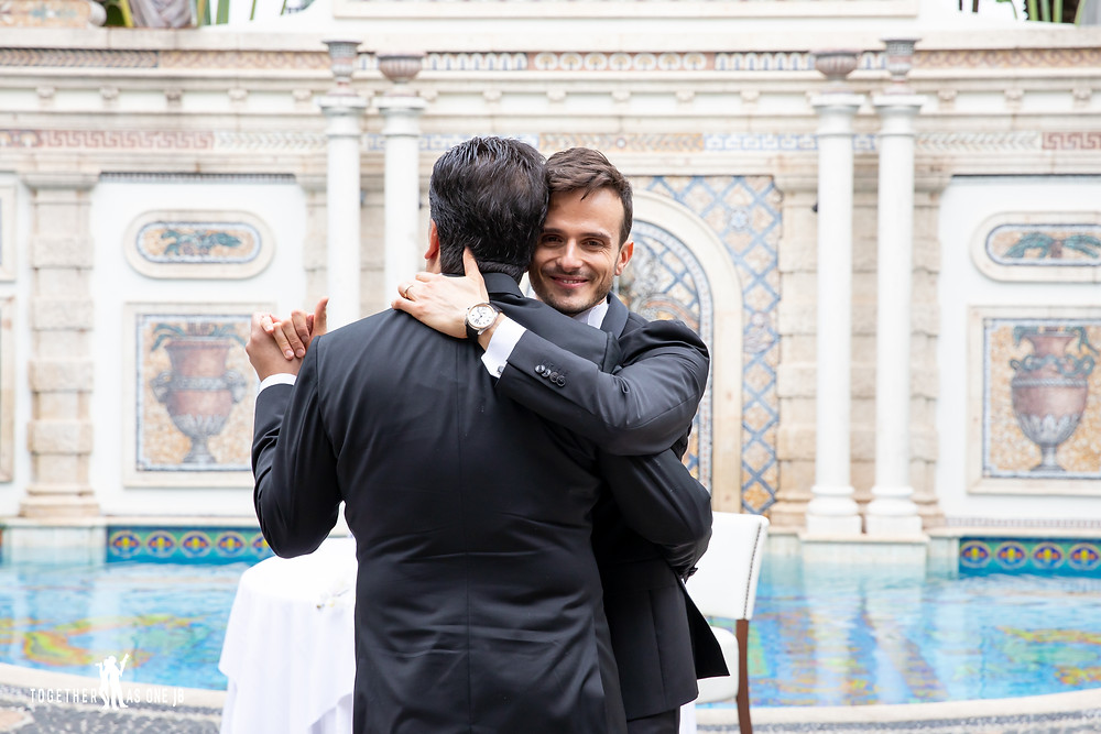 Grooms embrace during first dance in front of former Versace Mansion pool