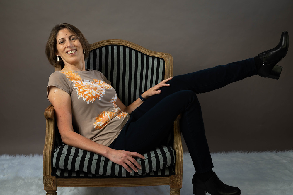Cincinnati portrait photographer captures image of woman sitting in chair with legs up in the arm rest.