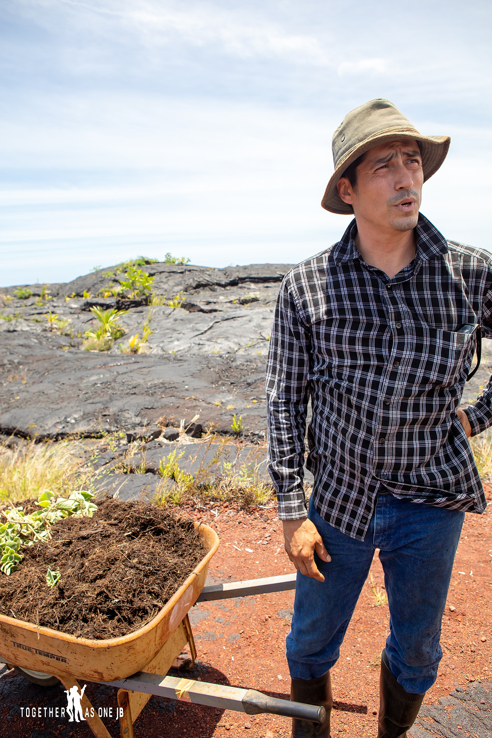 Volunteers from The Center for Getting Things Started with wheel barrow of mulch sharing his experience at the New Black Beach in Big Island Hawaii