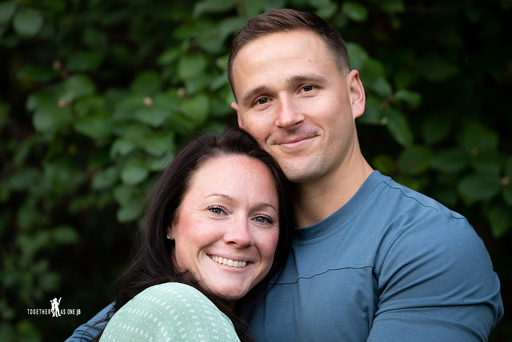 Cincinatti family photographer captures photography of young couple together hugging and smiling in yard.