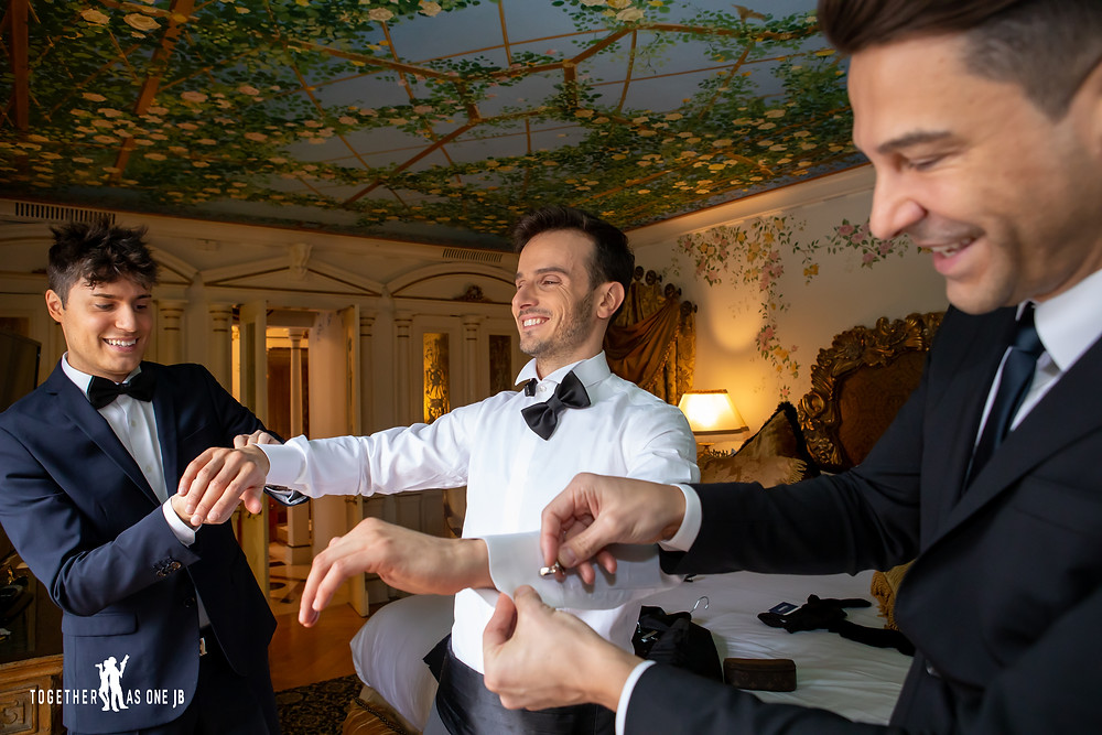 Best Men put on cuff links on groom before the wedding ceremony