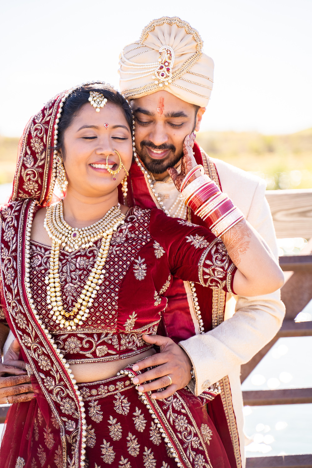 Indian wedding photographer captures image of indian husband and wife holding each other smiling.