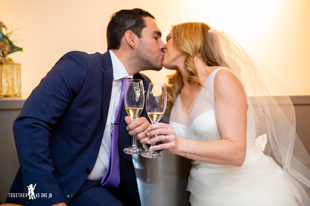 Bride and Groom kissing while champagne toast in the M Building in Wynwood