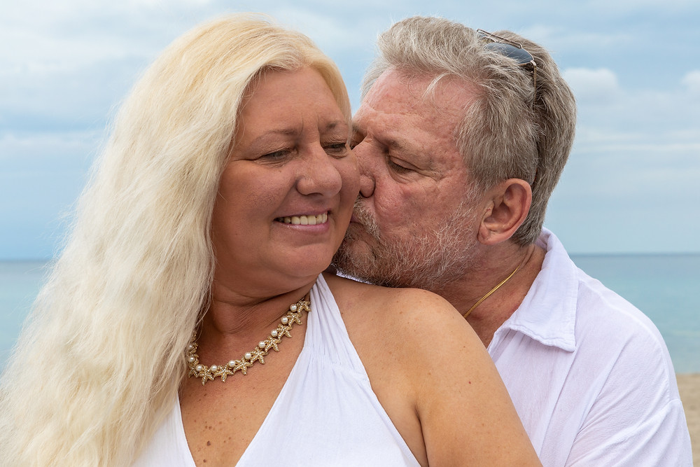 Cincinnati wedding photographer captures image of husband and wife kissing posing for a picture in the beach.
