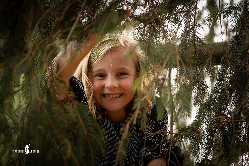 Cincinnati family photographer captures portrait photography of smiling daughter on tree behind pine leaves.
