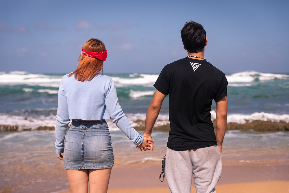 Destination photographer captures image of man and woman holding hands in the beach.
