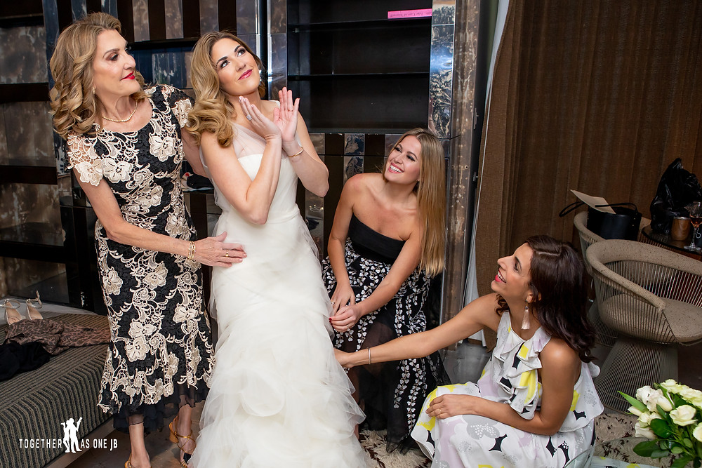 Bridesmaid and Mom helping bride put on dress in the bridal suite of the M building in Wynwood