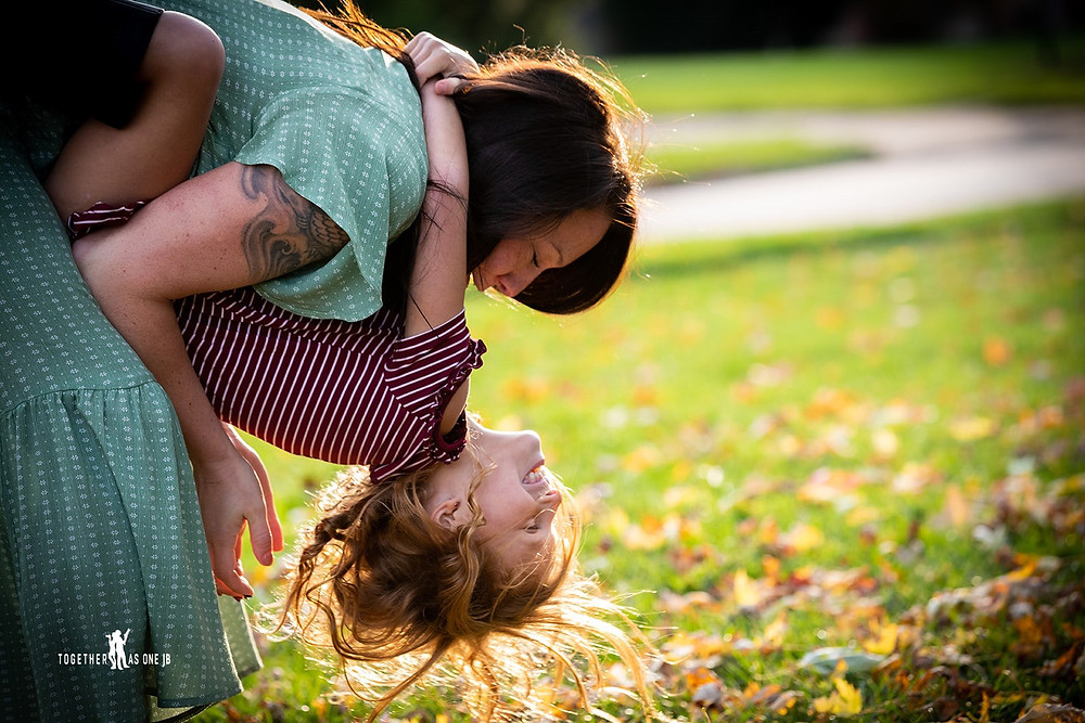 Cincinnati family photographer captures photography of mom playfully dipping smiling daughter in yard.