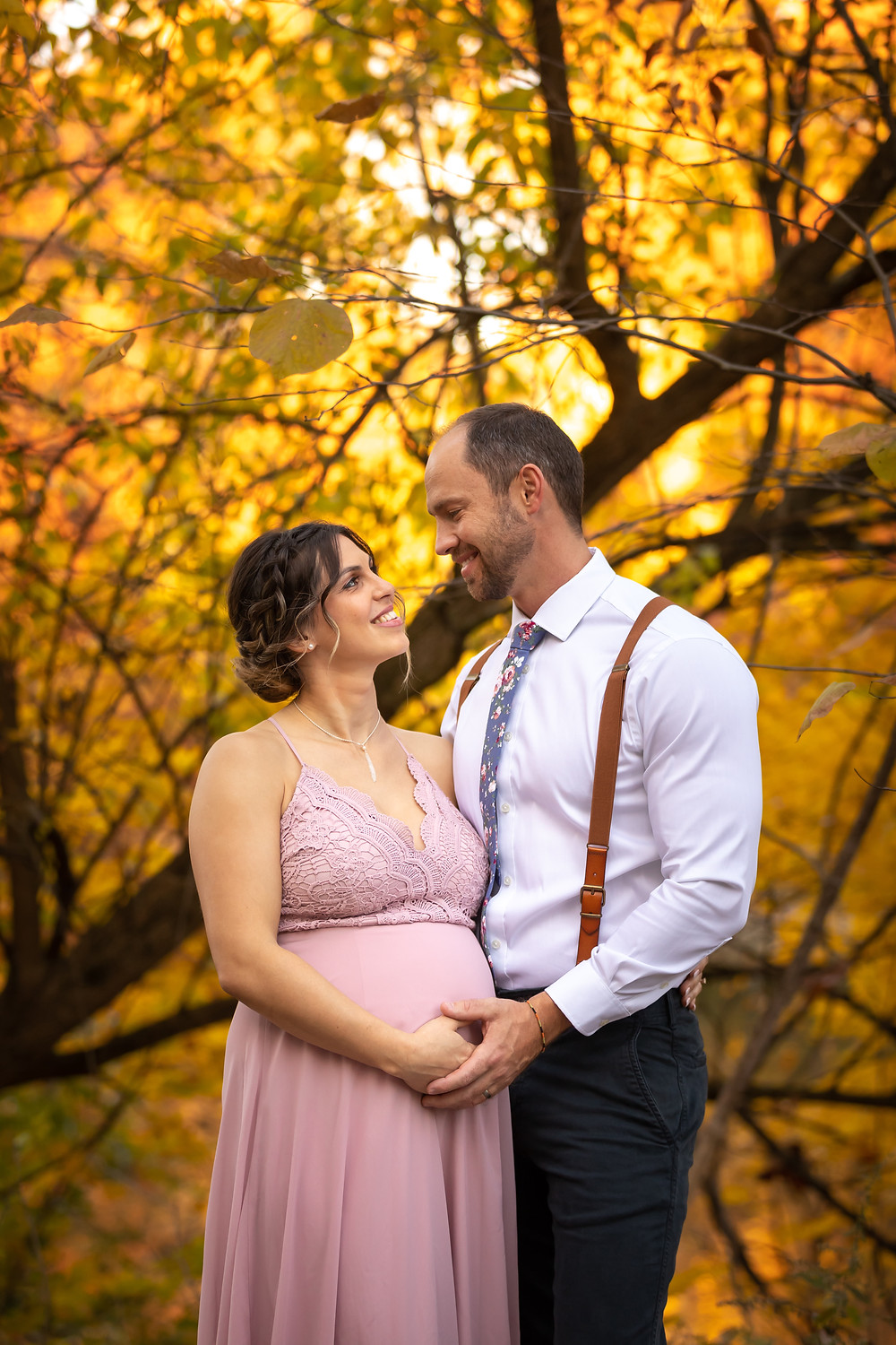 Cincinnati wedding photographer captures image of groom and bride hugging each other smiling under autumn trees.