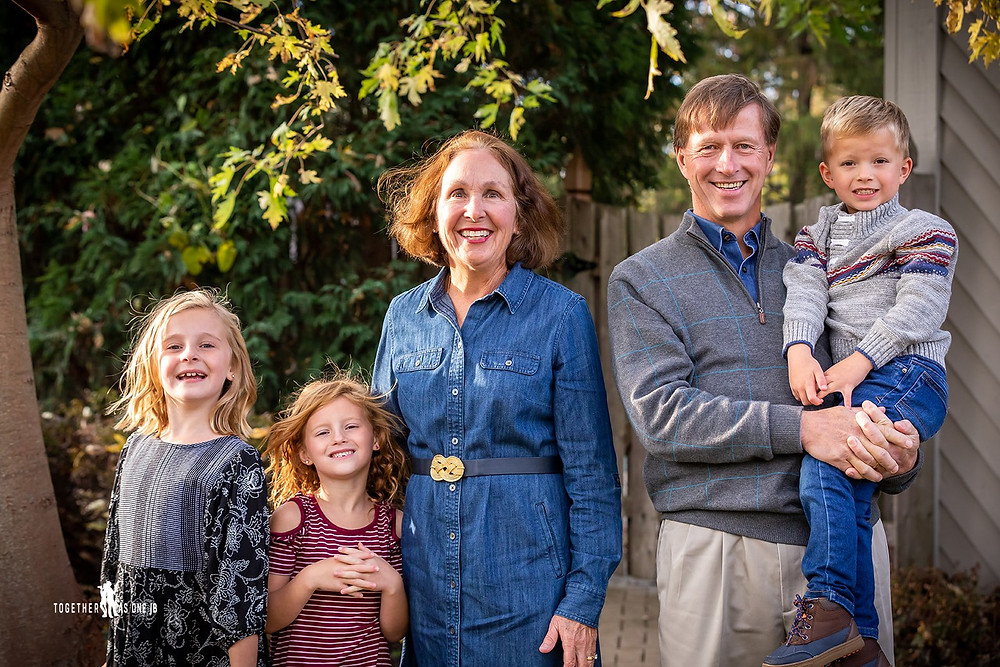 Cincinnati family photographer captures photography of happy family smiling in yard in autumn.