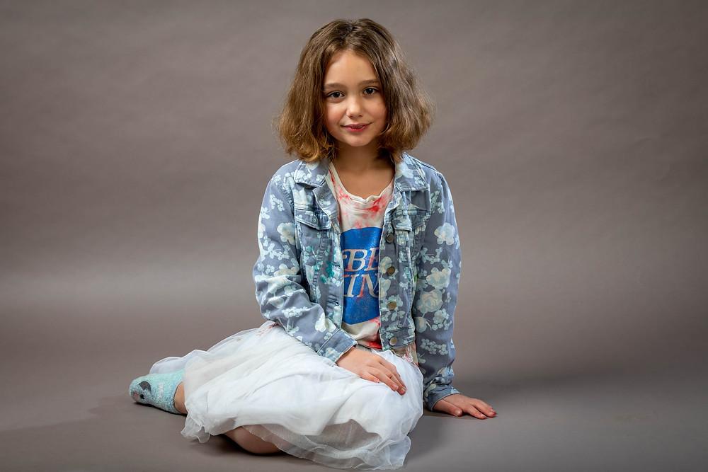 Cincinnati portrait photographer captures girl sitting on floor with hand on lap.