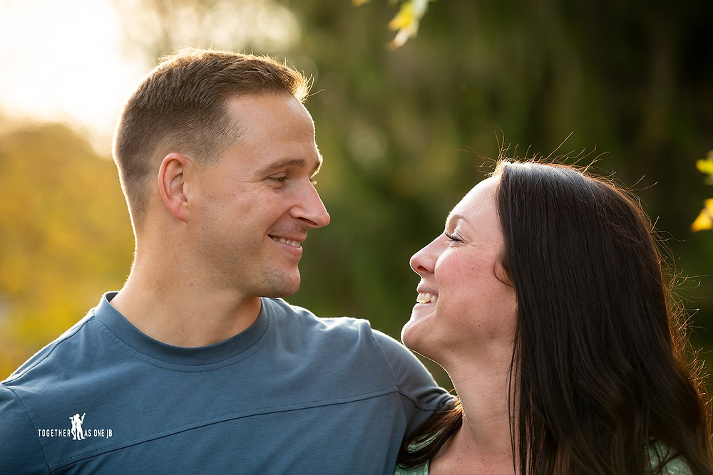 Cincinnati family photographer captures photography of  young couple smiling at each other under sunlight..
