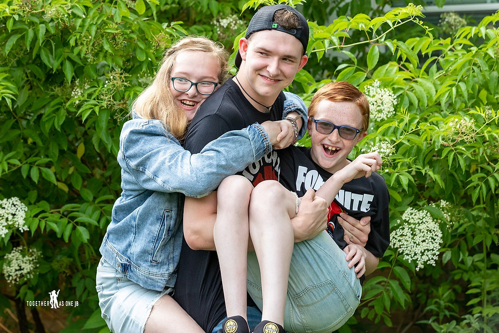 Cincinnati family photographer captures image of happy family hugging and carrying each other in yard.