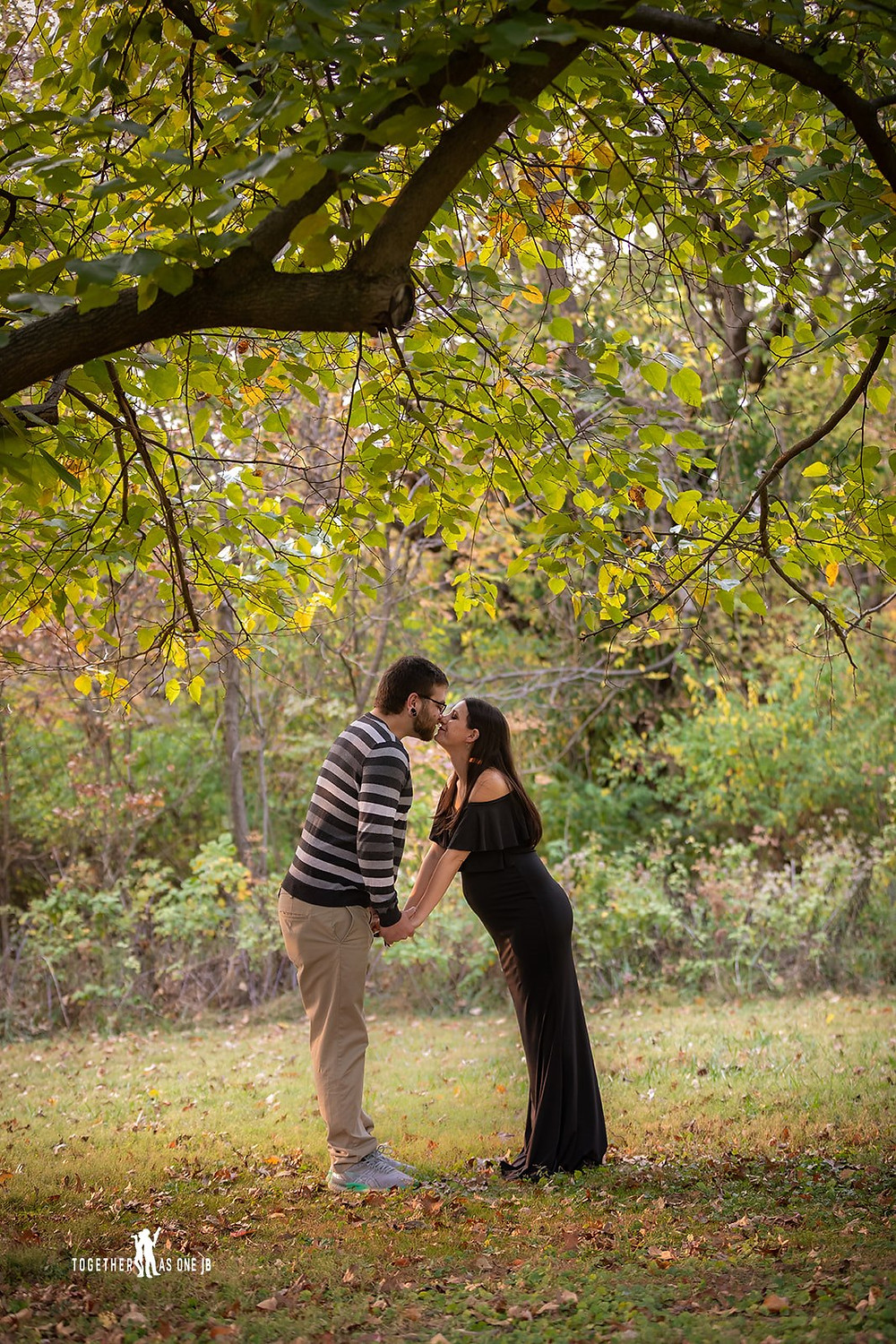 Cincinnati wedding photographer captures photograph of couple kissing under tree in the woods.