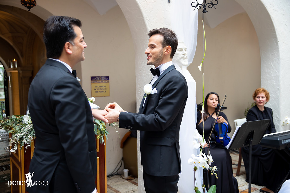 Groom places wedding ring on Groom during Wedding Ceremony