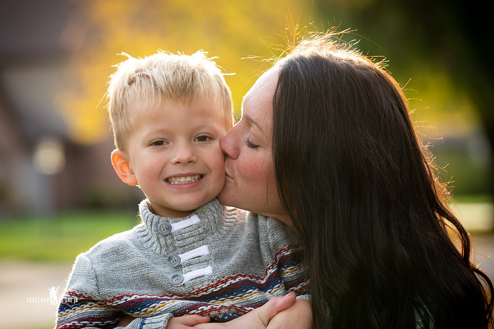 Cincinatti family photographer captures mother kissing cheek of son in autumn.
