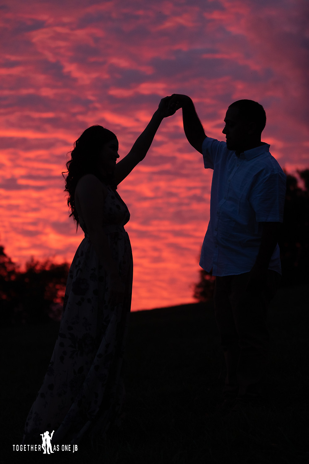 Twirl the bride sunset photo silhouette.  A beautiful photograph taken by Together As One JB of a recently engaged couple twirling the fiancé during sunset.