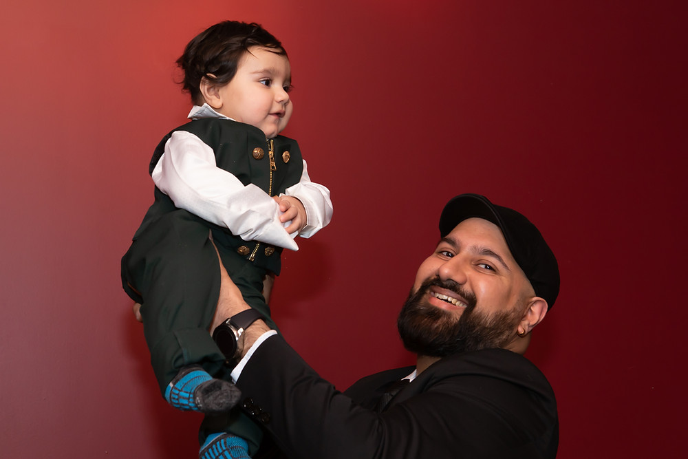 Indian birthday photographer captures image of indian father holding baby in air smiling.