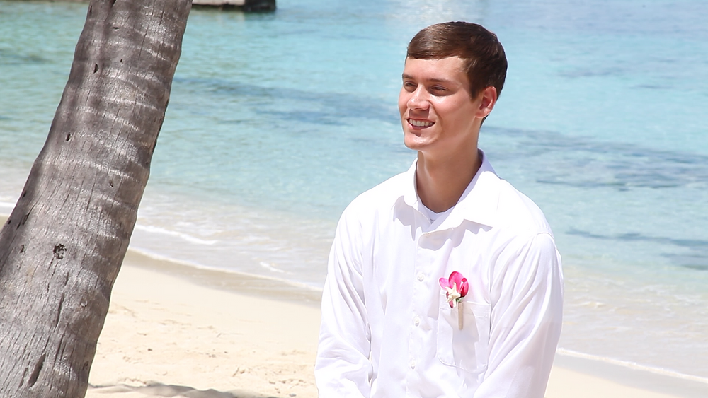 Cincinnati wedding photographer captures image of husband smiling under a palm tree in the beach.