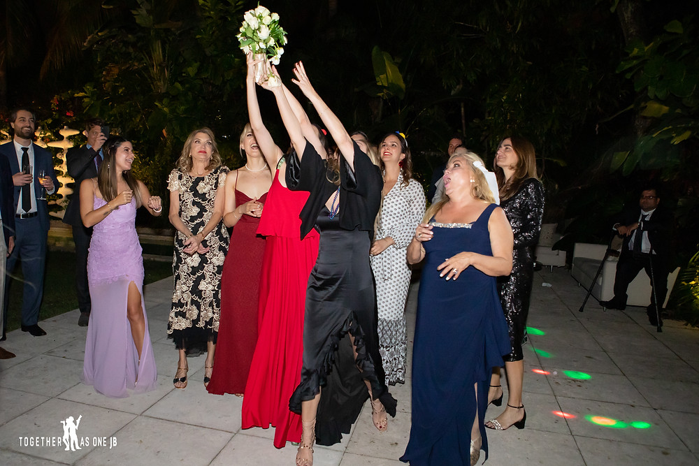 Single ladies catching wedding flower bouquet during wedding reception at the M Building in Wynwood