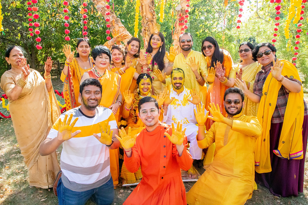 Indian wedding photographer captures image of indian family  performing the haldi ceremony smiling with yellow paste.