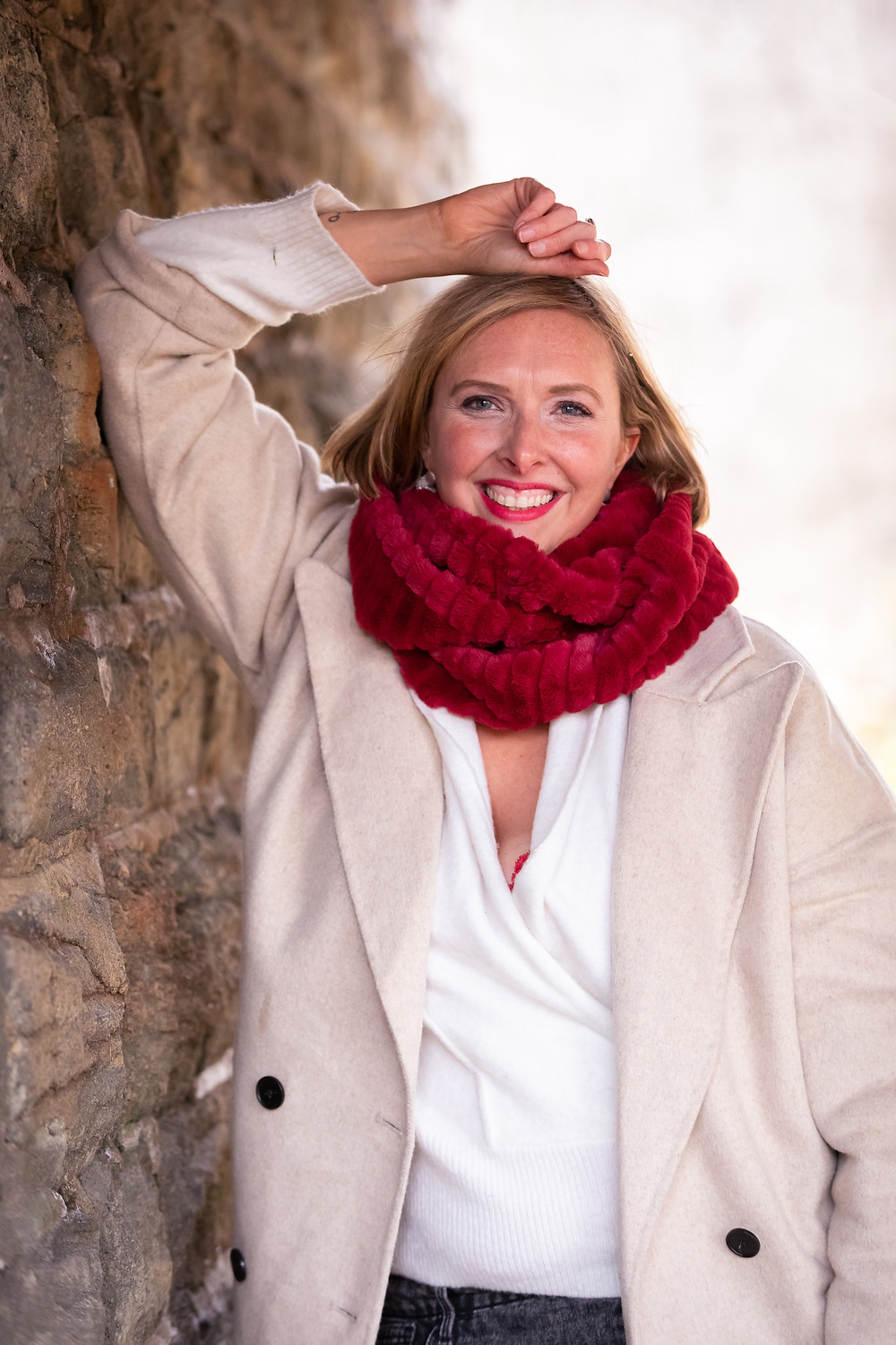 Cincinnati portrait photographer captures image of woman leaning on a wall smiling for a photo.