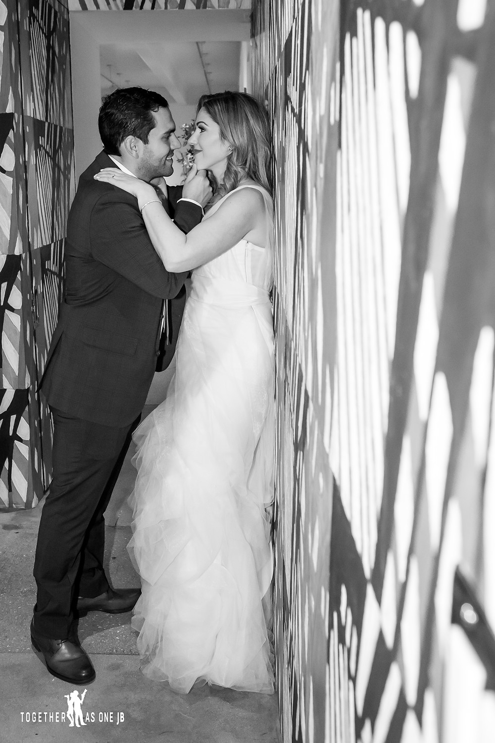 Groom kissing Bride in front of the wall mural in the M Building in Wynwood