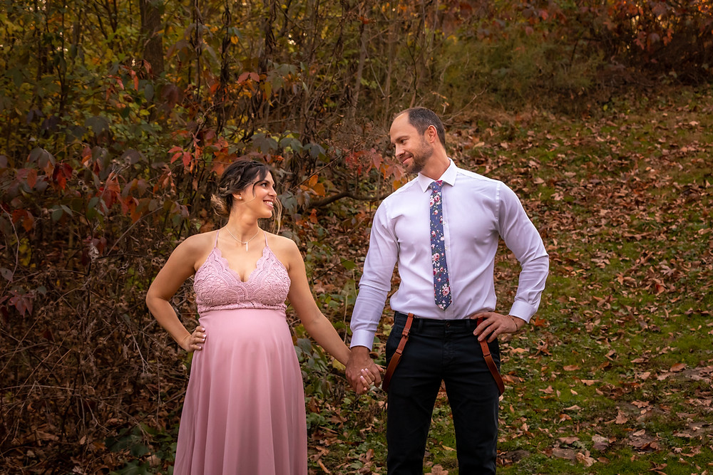 Cincinnati wedding photographer captures image of man and woman holding hands smiling and each other in forest.