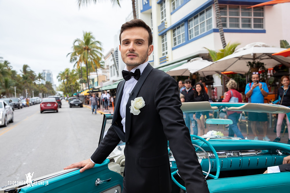 Groom looks at camera while standing in front of cuban car on Miami's busy South Beach street