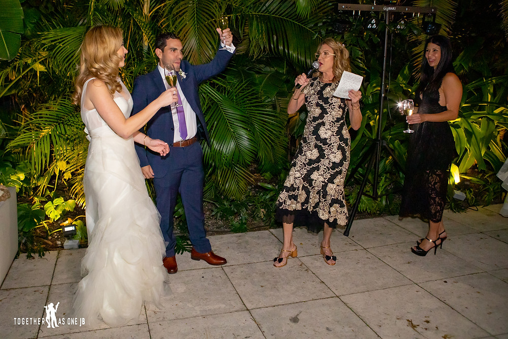 Wedding toasts by Mother of Groom while wedding couple cheers her on during wedding reception at the M Building in Wynwood