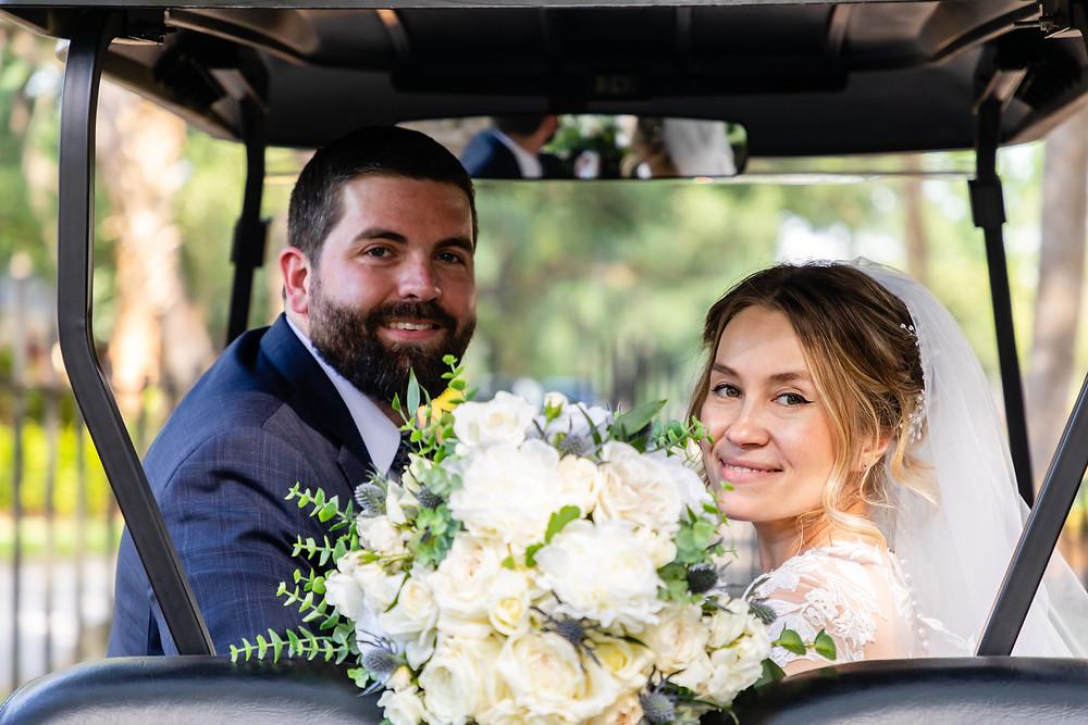 Cincinnatti wedding photographer captures image of bride and groom looking back from golf cart smiling.