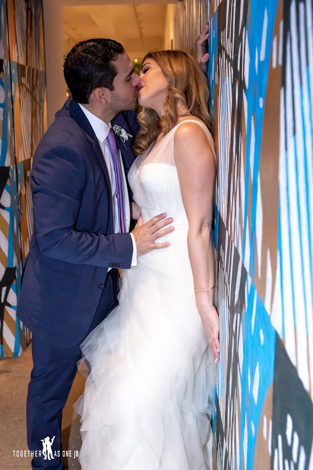 Bride and Groom kissing on wall mural in the M Building in Wynwood
