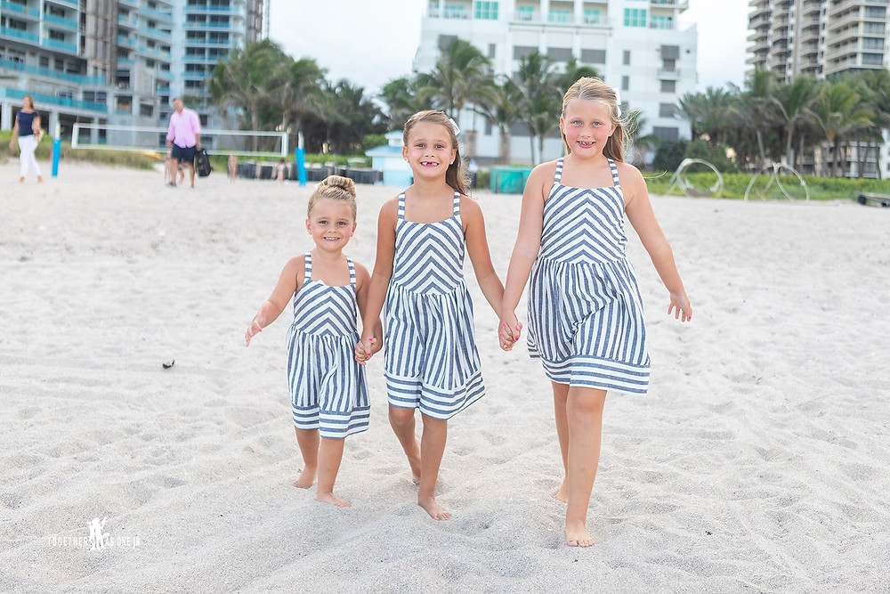 Cincinnati wedding photographer captures image of three little girls wearing matching outfits walking in the beach.