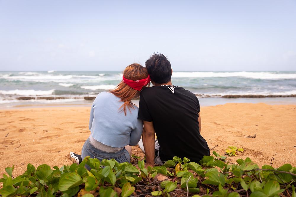 Destination photographer captures image of man and woman sitting in the beach leaning on each other.