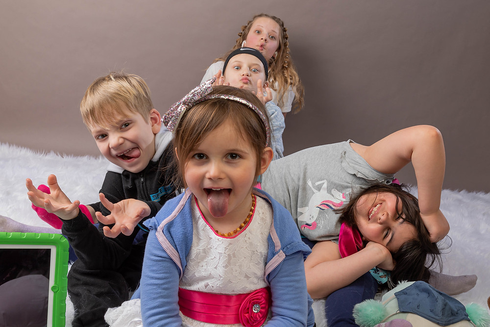 Cincinnati portrait photographer captures image of kids sticking their tongue out making funny faces to the camera one behind the other in a goofy way.