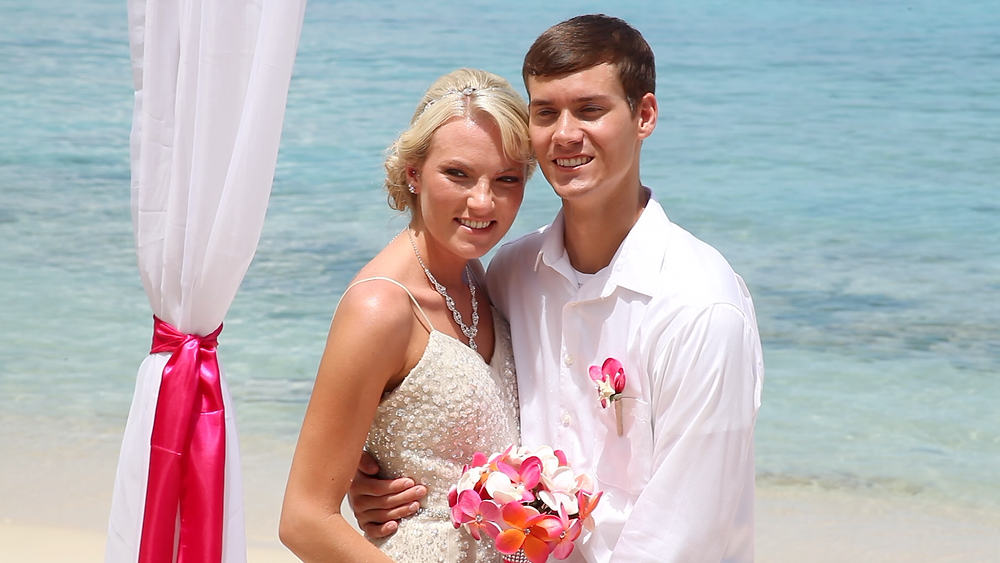 Cincinnati wedding photographer captures image of husband and wife smiling hugging each other in the beach with a bouquet of flowers.