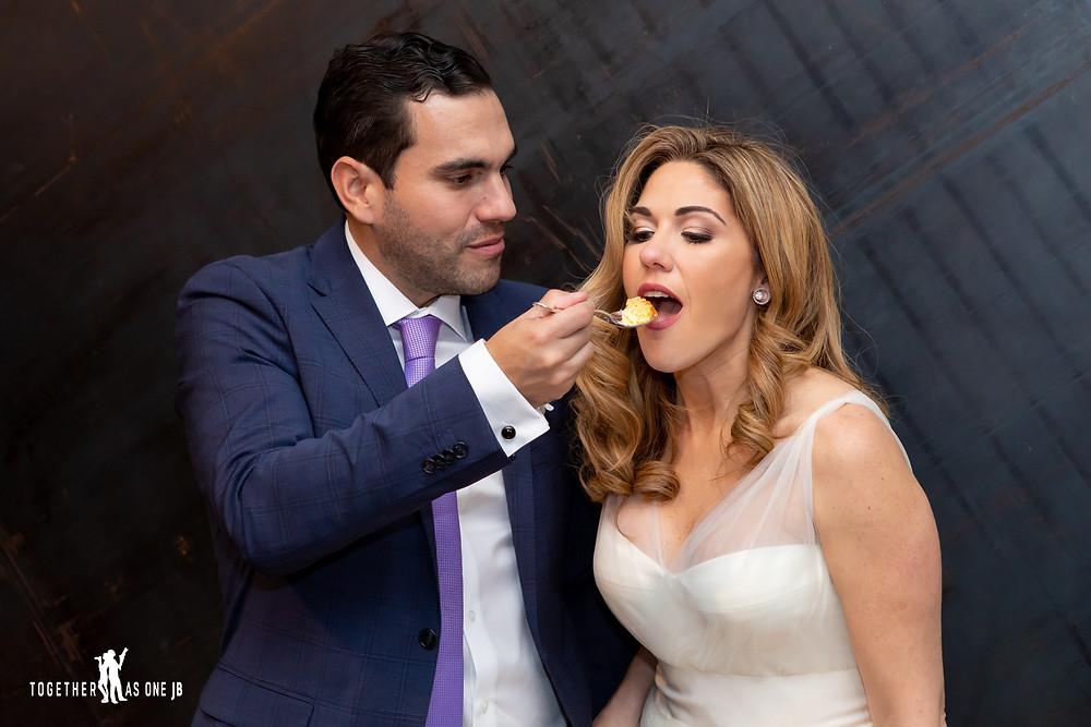 Groom feeding Bride at their wedding reception in the M Building in Wynwood