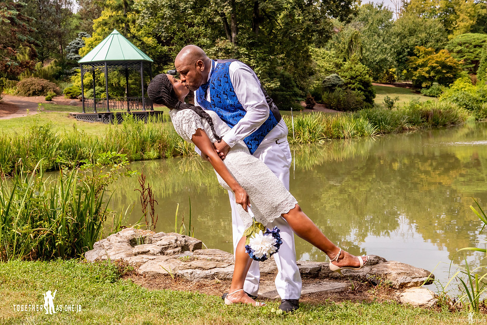 couple dipping and kissing with gazebo in the background after their small intimate wedding in Mt. Airy Park
