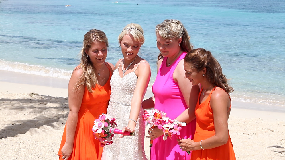 Cincinnati wedding photographer captures image of ladies laughing with bouquet of flowers in the beach.