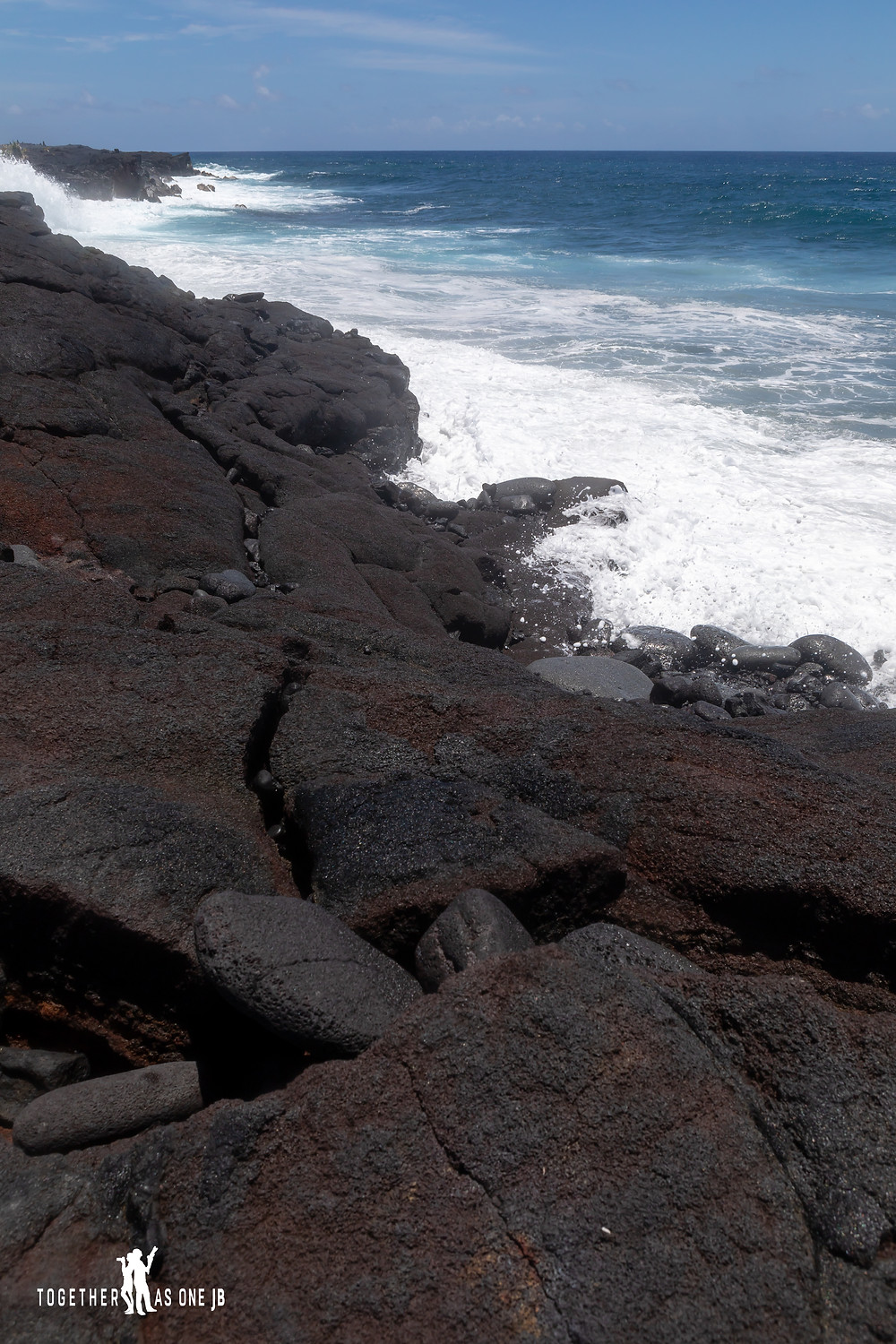 The shore of KAIMU KALAPANA NEW BLACK SAND BEACH  with the lava rocks and the white foam of the ocean waves