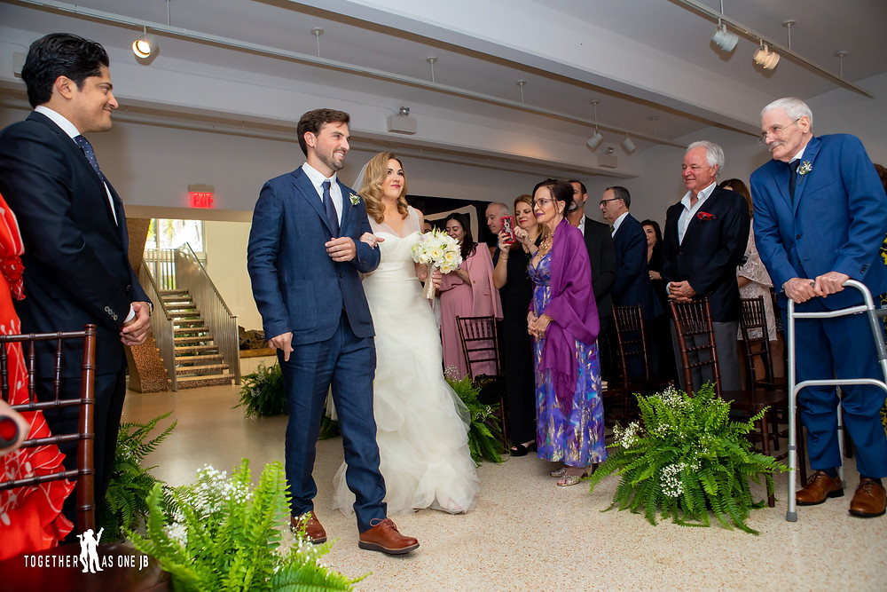 Bride walking down aisle with brother while father of the bride watch