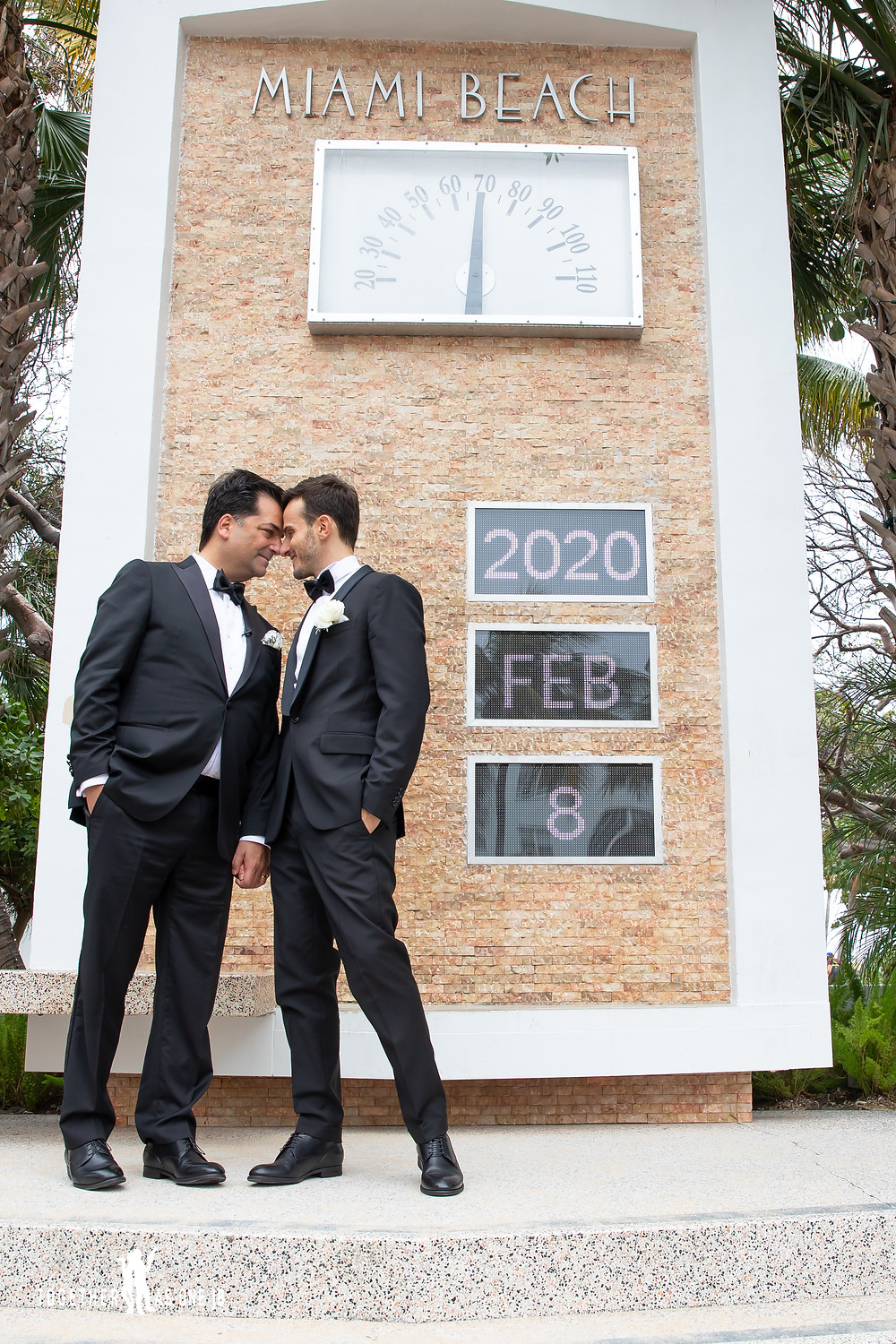 Grooms hold hands with foreheads touching while standing in front of famous Miami Beach sign of date and temperature in South Beach Miami
