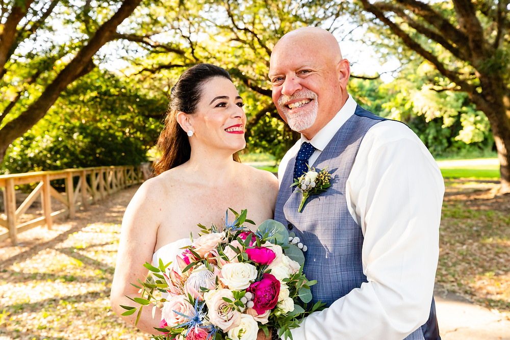 Cincinnati wedding photographer captures image of husband and wife smiling holding a bouquet of flowers in the park.